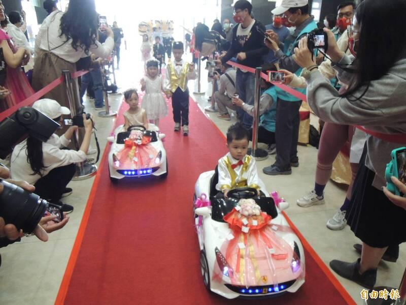 小花童駕著玩具電動車進入會場,現場喜氣洋洋。(記者張勳騰攝)
