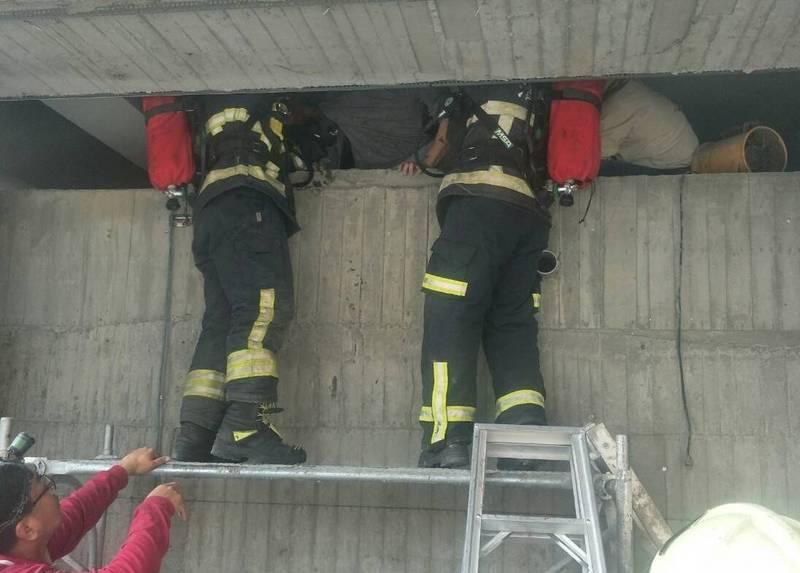 消防人員爬進蓄水池內救人。(消防局提供)