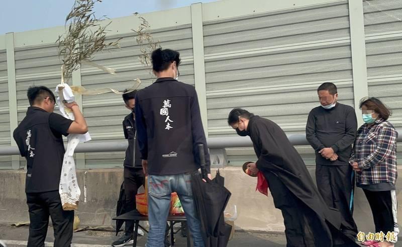 根女父母在西濱快速道路上招魂,神情哀悽。(記者歐素美攝)