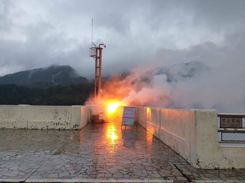 北水局在石門水大壩頂進行人工增雨,燃放1支焰劑。(記者李容萍翻攝)