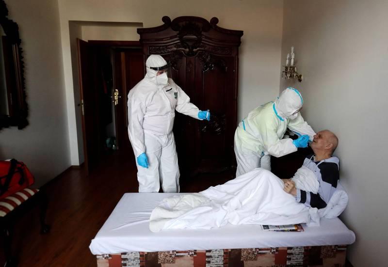 捷克2度感染武漢肺炎的痊癒患者暴增。圖為首都布拉格的醫護人員22日為民眾進行鼻咽拭子檢測。(路透)