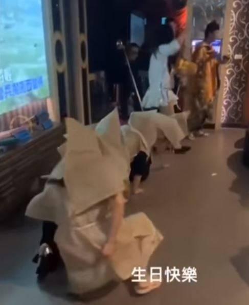 臉書社團「黑色豪門企業」24日上傳一段「挑戰2021年最狂慶生」抖音影片,一群人在KTV裡,其中4人披麻戴孝在地上跪爬。(圖擷取自臉書社團「黑色豪門企業」影片)