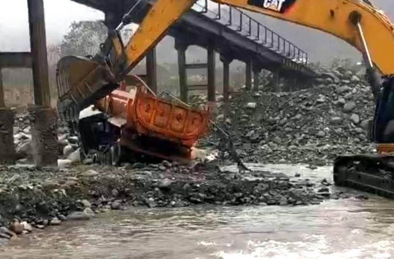 南投縣信義鄉卓棍溪與濁水溪匯流水域,發生砂石車翻落意外,並出動大型挖土機進行拖吊情形。(記者謝介裕翻攝)