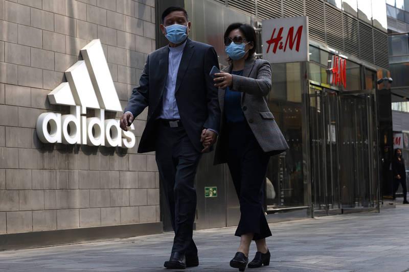 H&M、adidas等國際大品牌因表態拒用新疆血汗棉花遭中國抵制報復,話題討論度持續增長。圖為北京相關品牌門市。(美聯社)