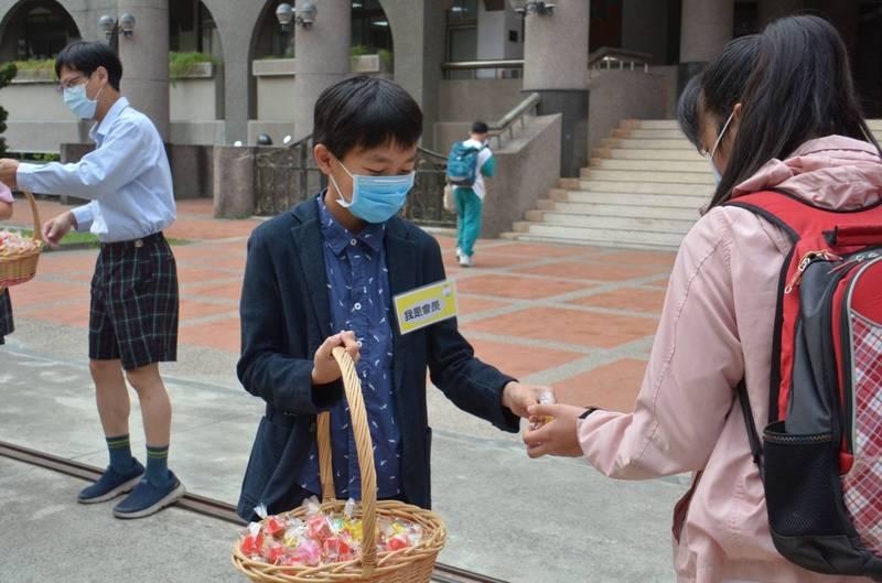 嘉義市大同國小的自治市小市長梁定洵,今天在校門口扮成家長會長發糖果。(大同國小提供)