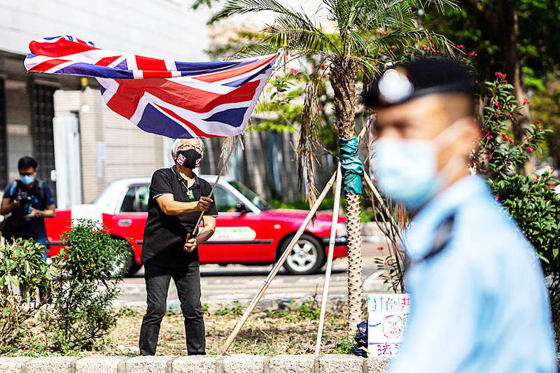 Democracy advocate Alexandra Wong, left, also known as Grandma Wong, waves a Union flag outside a West Kowloon court in Hong Kong yesterday. Photo: AFP