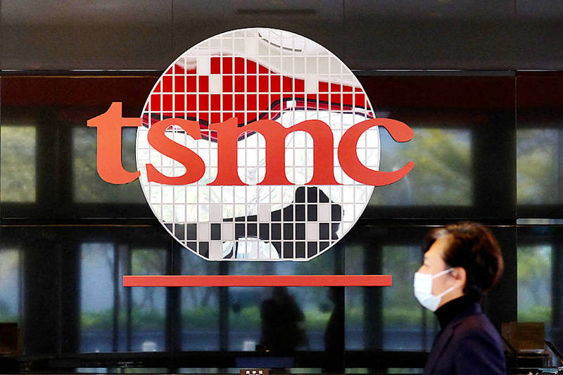 A man walks past the company logo of Taiwan Semiconductor Manufacturing Co, the world's largest semiconductor maker, in Hsinchu on Jan. 29. Photo: Sam Yeh, AFP