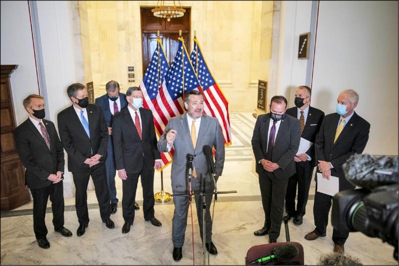 美國德州參議員克魯茲3月24日在華府國會山莊的記者會上發言時,拒絕應記者要求戴上口罩,但他身邊的同僚全都戴著口罩。(彭博)