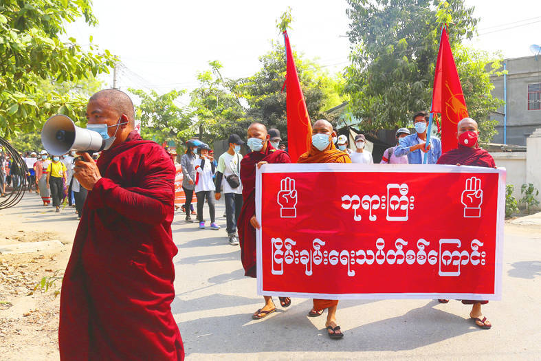 """Demonstrators hold a banner that reads: """"PhaYarGyi Peace Strike Troop"""" during a protest against the military coup in Mandalay, Myanmar, yesterday. Photo: EPA-EFE"""