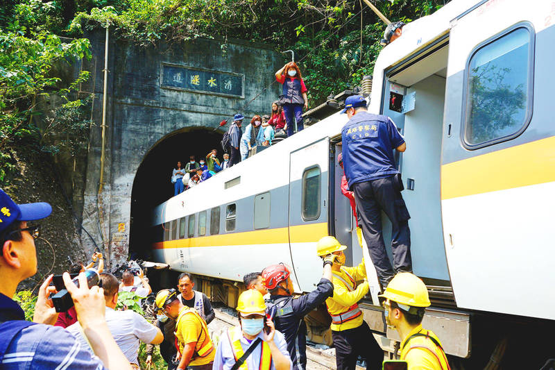 Passengers on a train that was derailed in Hualien yesterday leave the train by walking on the roof. Photo: CNA