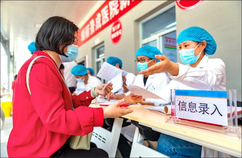 一名女性一日前往雲南瑞麗的景成醫院登記資料以便接種疫苗。(法新社)
