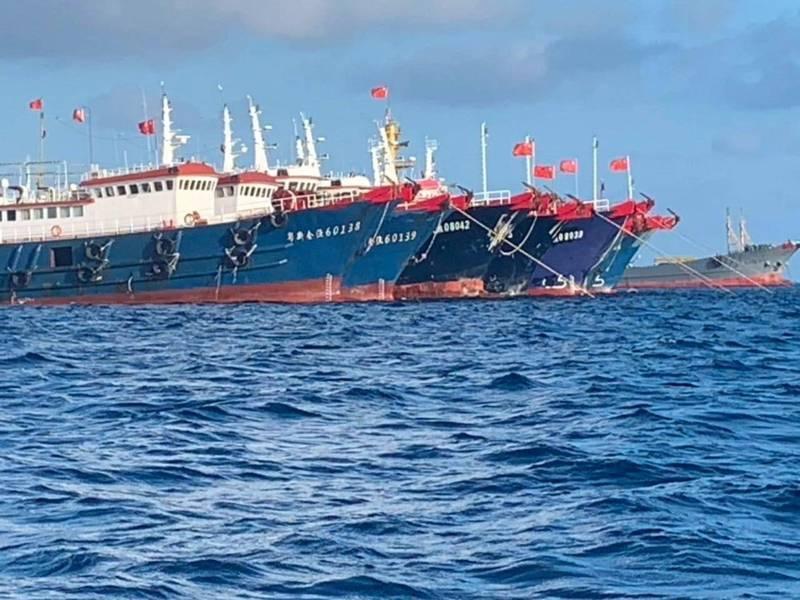 菲律賓官方3日27日拍攝到中國船隻集結在牛軛礁,高掛五星旗,就地錨泊,不肯離去。(路透)