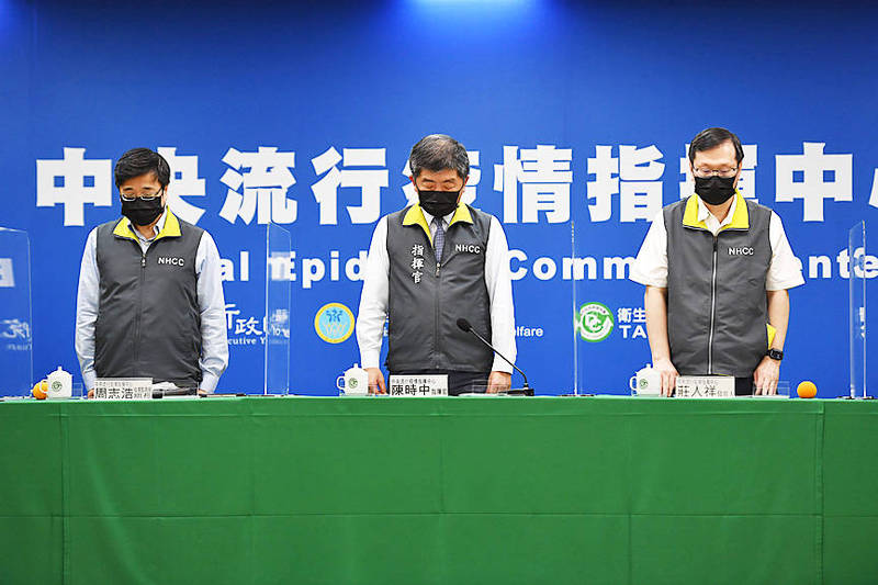 From left: Centers for Disease Control (CDC) Director-General Chou Jih-haw, Minister of Health and Welfare Chen Shih-chung and CDC Deputy Director-General Chuang Jen-hsiang stand for a minute's silence at the start of a news conference at the Central Epidemic Command Center in Taipei yesterday to mourn the victims of Friday's train crash in Hualien County. Photo: CNA