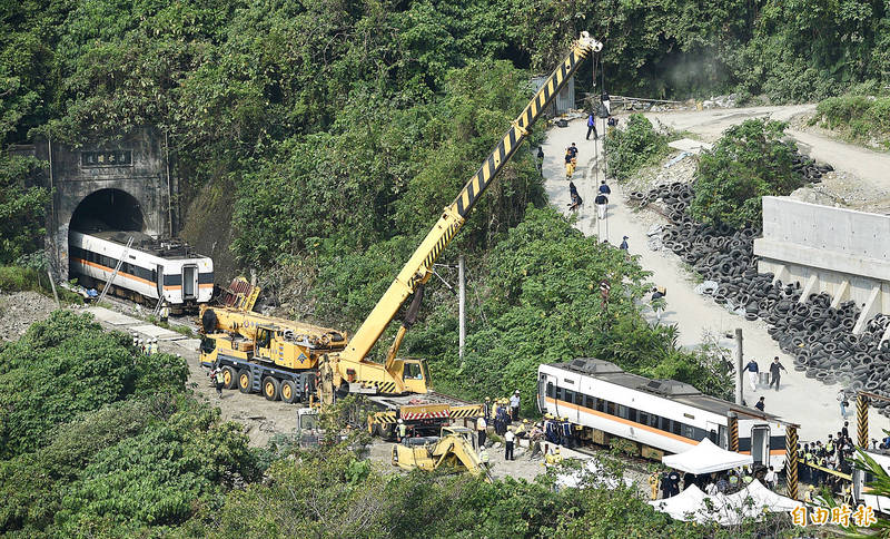 A crane yesterday moves train carriages at the entrance of the Cingshuei Tunnel in Hualien County's Sioulin Township after Friday's crash. Photo: Peter Lo, Taipei Times