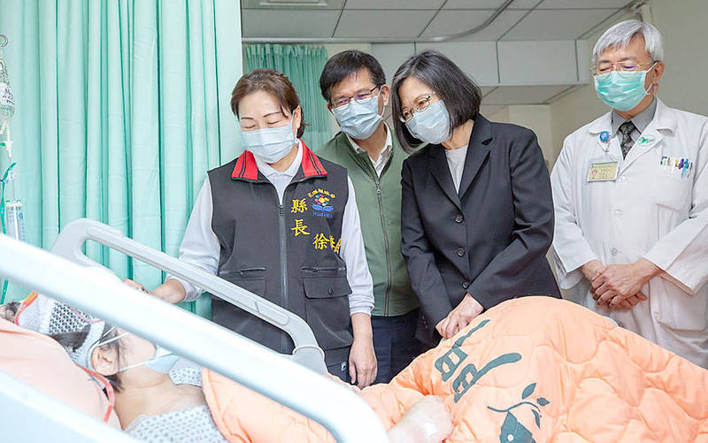 President Tsai Ing-wen, second from left, yesterday visits a person who was injured in Friday's Taroko Express No. 408 crash in Hualien County. Photo: Taiwan Presidential Office / AFP