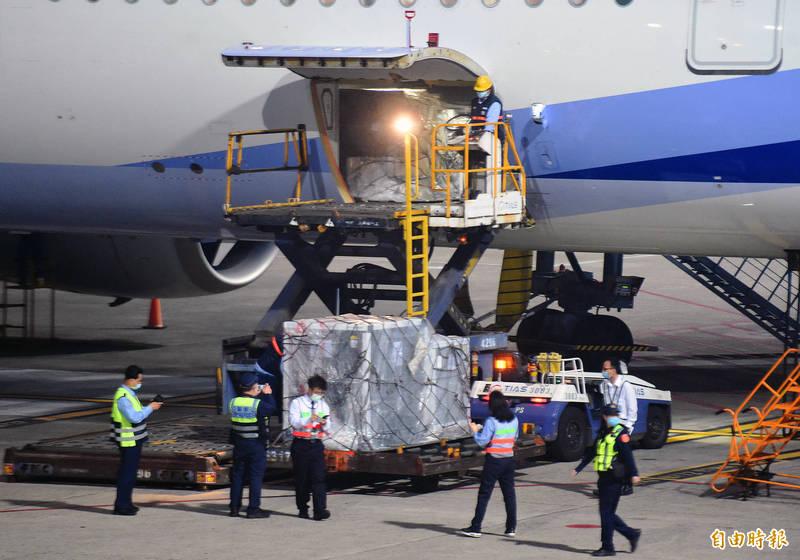 首批自COVAX(COVID-19疫苗全球取得機制)取得的十九.九二萬劑AZ疫苗,4日凌晨五時三十分自荷蘭阿姆斯特丹運抵桃機運抵桃園國際機場,裝載的疫苗盤櫃運下飛機,並由海關及疾管署官員在機坪檢視相關書面表單後,在航警戒護下運往冷鏈倉儲存放。(記者朱沛雄攝)