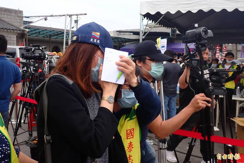 袁淳修司機員的妻子(左)頭戴棒球帽遮臉,相當悲傷。(記者花孟璟攝)
