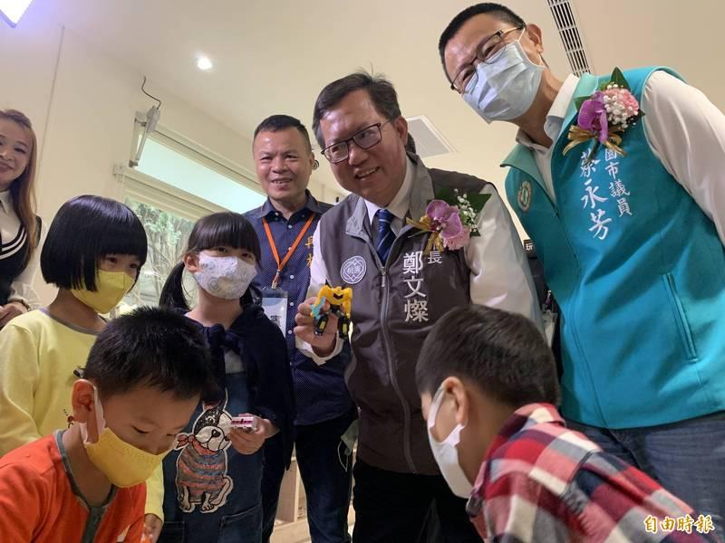 市長鄭文燦(右二)拿著二手玩具要和小朋友交換。(記者陳恩惠攝)