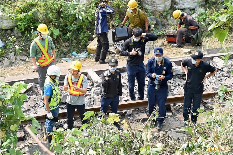 台鐵太魯閣號撞擊滑落軌道的吊貨車,造成死傷慘重,鐵路警察昨在事故車廂拖移作業時拍照蒐證。(記者塗建榮攝)