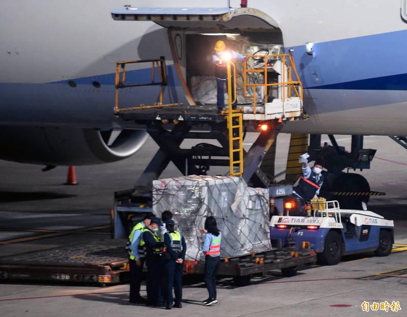 首批自COVAX(COVID-19疫苗全球取得機制)取得的AZ疫苗,4日凌晨5時30分自荷蘭阿姆斯特丹運抵桃機運抵桃園國際機場,裝載的疫苗盤櫃運下飛機,並由海關及疾管署官員在機坪檢視相關書面表單後,在航警戒護下運往冷鏈倉儲存放。(記者朱沛雄攝)