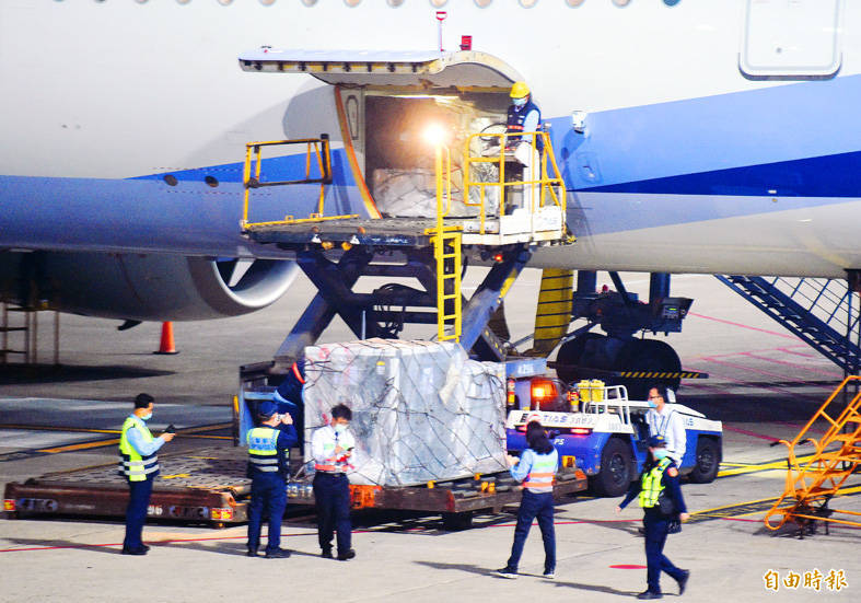 The first batch of COVID-19 vaccines allocated to Taiwan through the global vaccine sharing program COVAX is offloaded after its arrival at Taiwan Taoyuan International Airport yesterday. Photo: Chu Pei-hsiung, Taipei Times