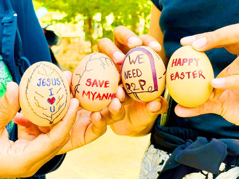 People hold eggs painted with protest slogans in Mandalay, Myanmar, on Friday. Photo: Reuters