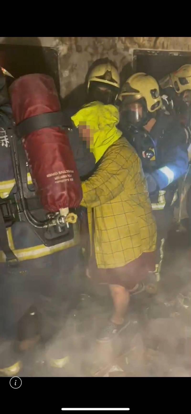 消防人員將李母救出火場,送醫後插管治療中。(記者徐聖倫翻攝)