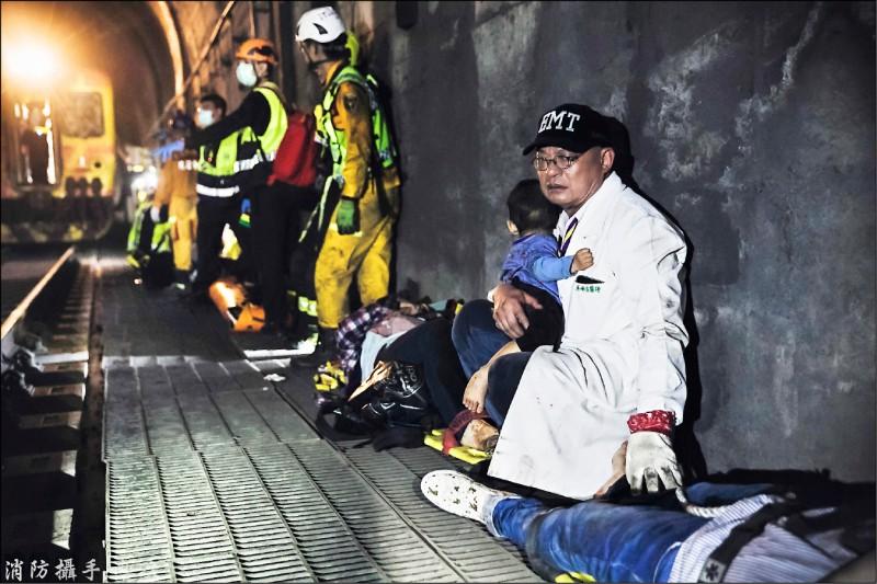 吳坤佶抱著倖存的男童,蹲坐在隧道邊安撫他。(消防攝手蔡哲文提供)
