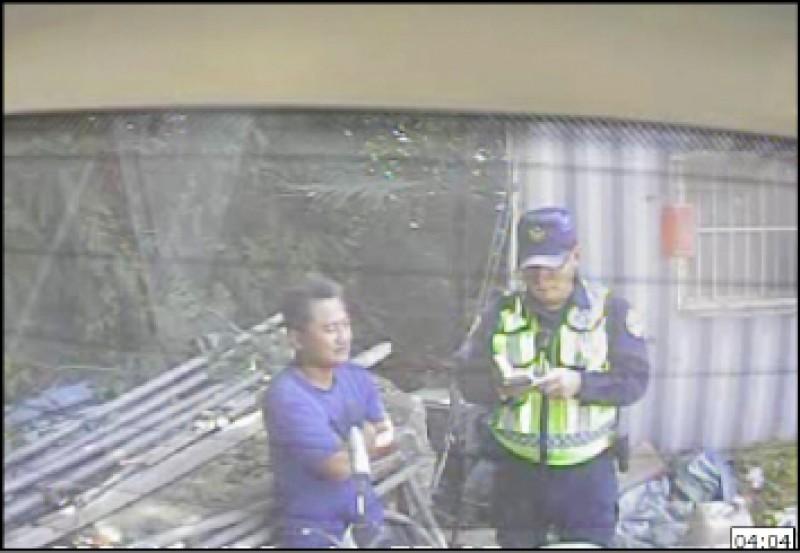 義祥工業社老闆李義祥(左一)事發後只在工寮前與友人聊天,一副事不關己,警方上前盤查身份。(記者王錦義翻攝)