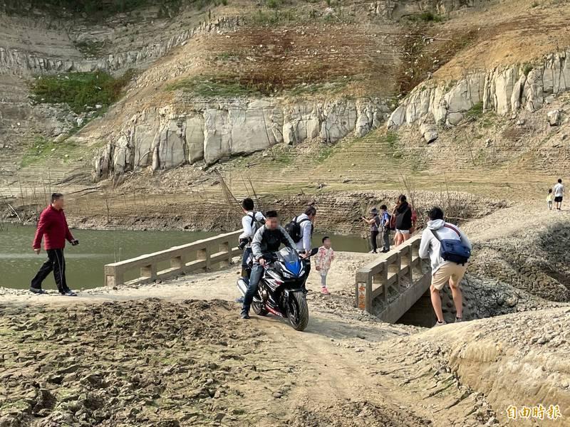 永和山水庫底的永安橋重現,意外成為民眾探訪的熱門景點,卻也衍生機車騎士亂入騎乘的亂象。(記者彭健禮攝)