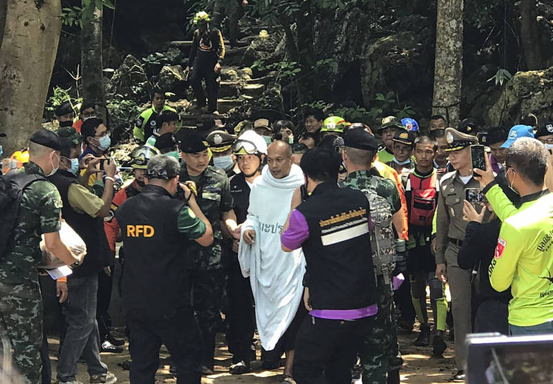 馬納斯(白衣者)上週六到彭世洛府一處洞穴打坐,沒想到突如其來一場暴雨,讓他受困洞穴中,週三終於被平安救出。(美聯社)