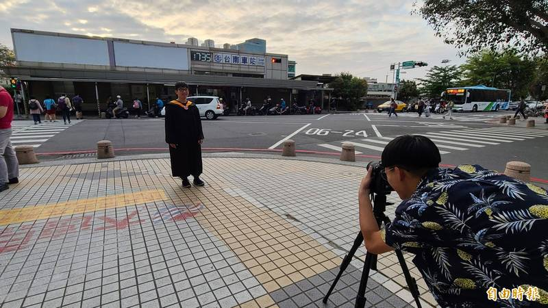 台鐵台南車站舊後站即將拆除,有成大應屆畢業生於舊後站營運最後一天前往拍攝畢業照片。(記者劉婉君攝)