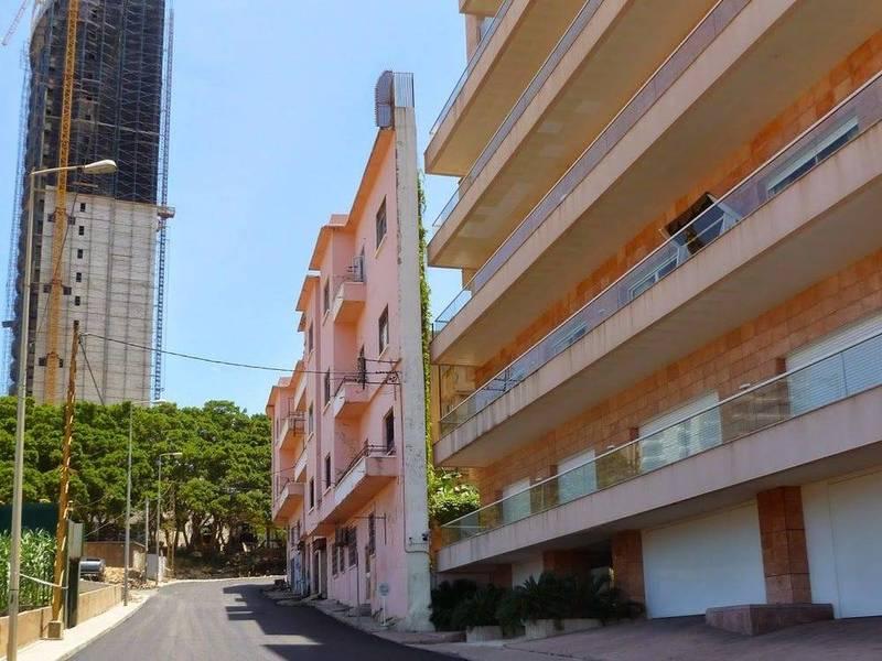 黎巴嫩貝魯特馬納拉街區,蓋著一座窄如牆壁的房屋,擋住後面豪宅的海景第一排。(圖翻攝自beirutbitchh推特)