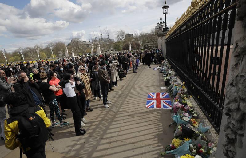 英國民間哀傷不已,許多民眾聞訊後紛紛捧著花束前往白金漢宮致哀。(美聯社)