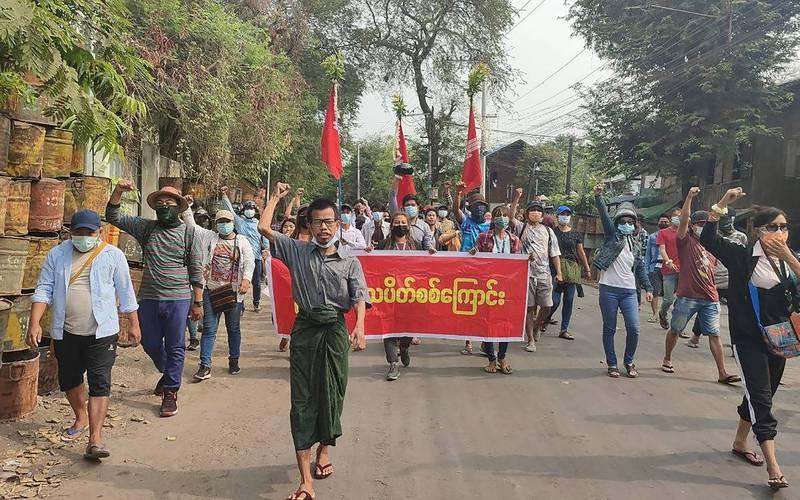 緬甸軍政府不斷打壓新聞自由,不惜斷網、降低流量阻止民眾以網路傳遞訊息。圖為緬甸示威人士今天拿著布條上街抗議。(法新社)