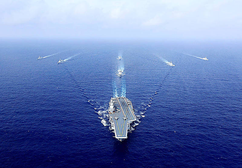 Chinese aircraft carrier the Liaoning, bottom, sails during a drill on April 18, 2018. Photo: AFP