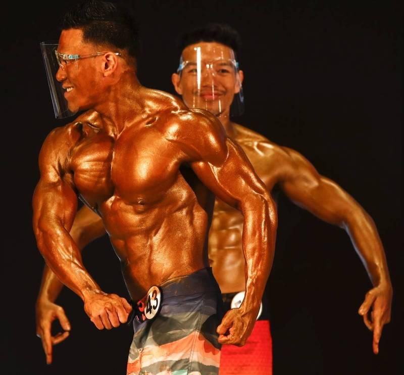 2021年泰國先生健美比賽9日在曼谷舉行,參賽者展示健壯的肌肉時戴防護面罩,作好防疫措施。(歐新社)