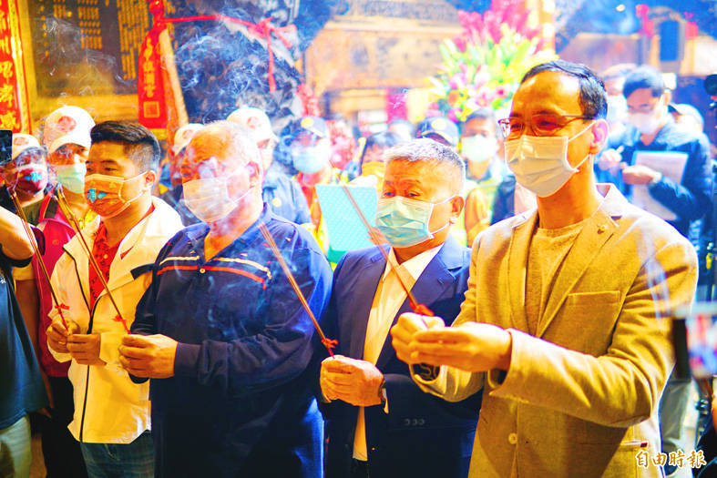 Former Chinese Nationalist Party (KMT) chairman Eric Chu, right, Jenn Lann Temple chairman Yen Ching-piao, second right, Yen's son, former KMT legislator Yen Kuan-hen, left, and independent Taichung City Councilor Chang Tsang-yi, second left, pray at Jenn Lann Temple in Taichung's Dajia District on Friday. Photo: Ho Tsung-han, Taipei Times