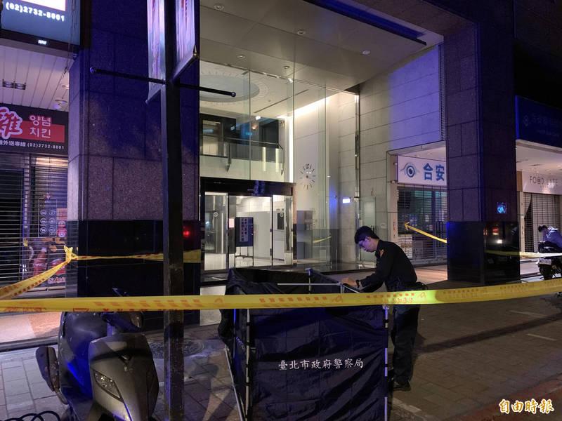 台北市基隆路一棟大樓今晚驚傳有男子自樓頂墜落人行道,當場身亡,警方到場後拉起封鎖線調查。(記者姚岳宏攝)