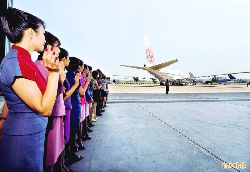 China Airlines Ltd flight crew and ground staff wave as a Boeing 734-400 plane leaves the company's maintenance hangar at Taiwan Taoyuan International Airport yesterday. Photo: Chu Pei-hsiung, Taipei Times