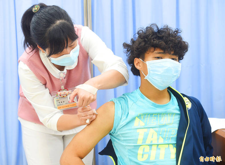 A nurse adminsters a COVID-19 vaccine to Chinese Taipei Football Association representative Yu Chia-huang yesterday in Taipei. Photo: Chien Jung-fong, Taipei Times