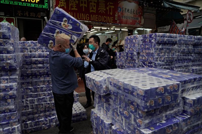 去年2月,香港因武漢肺炎疫情爆發引發衛生紙搶購潮,一家商店擺出大批衛生紙販售,店主因貨物擋路遭警方質問。(美聯社資料照)