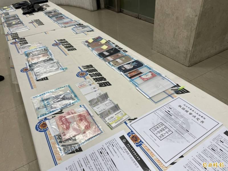 警方查扣手機、筆電、行動網卡、提款卡等大批贓證物。(記者邱俊福攝)