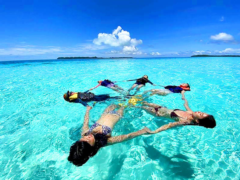 People float in the sea at a beach in Palau in an undated photograph. Photo courtesy of a travel agency
