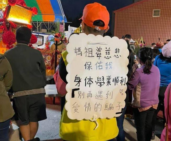 一名信徒背著一塊牌子向媽祖祈求不要再遇到「愛情的騙子」。(圖取自臉書社團「爆料公社(官方粉專專屬)」)
