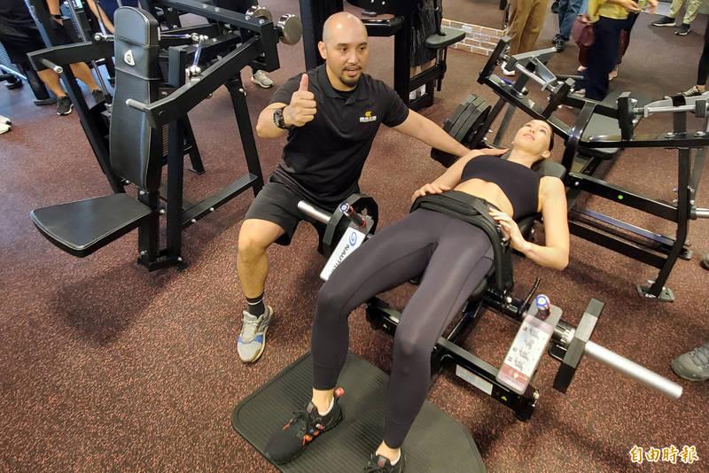 健身工廠教練與代言人Akemi示範示範今夏最夯健身器材。(記者張忠義攝)