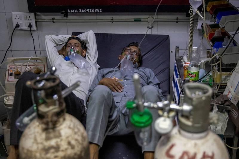 印度首都新德里醫院的病床不足,兩名患者必須共躺一張病床。(路透)