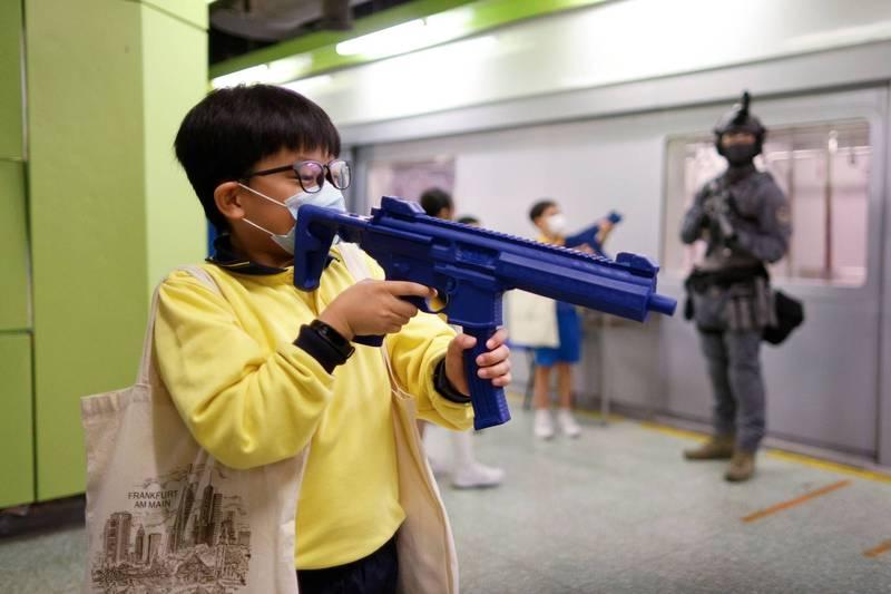 學生持玩具衝鋒槍於車廂內嬉戲。(路透)