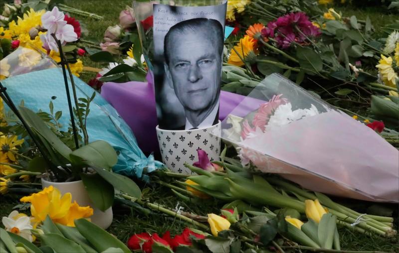 英國女王夫婿菲利浦親王辭世隔天的10日,溫莎古堡大門外擺滿悼念花束與菲利浦的照片。(美聯社)