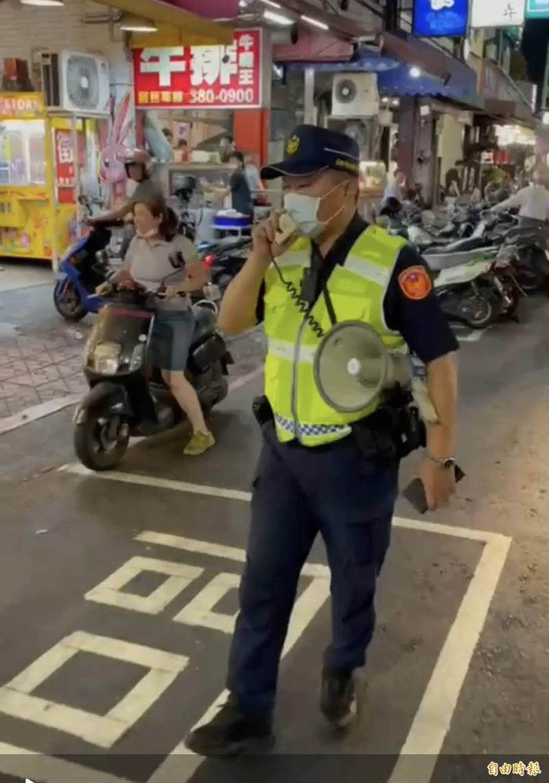警方持「大聲公」宣導不要違停。(記者黃旭磊攝)